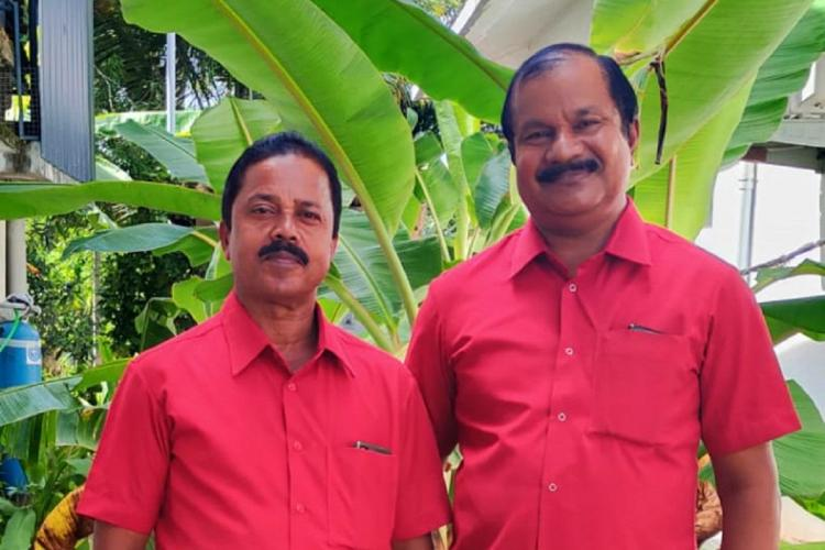 Udayakumar shorter and Raveendran taller are standing next to each other wearing red shirts against a banana leaf plant