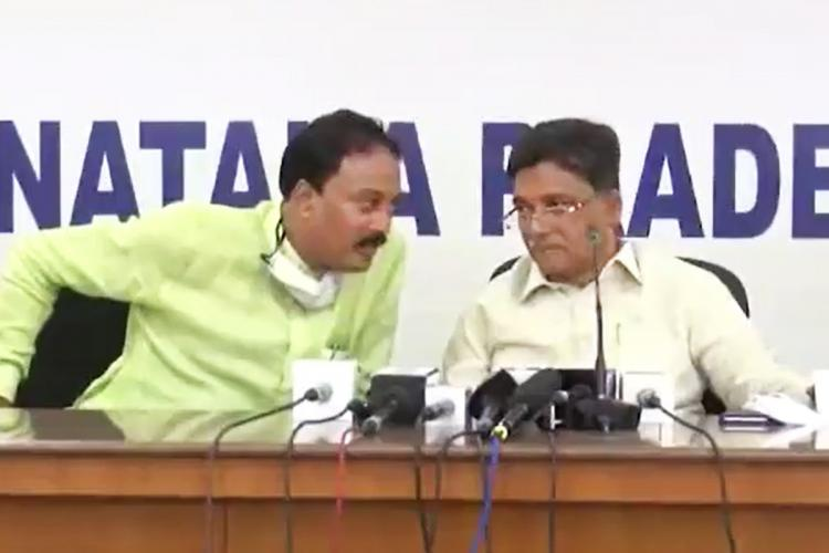 - Former Lok Sabha member VS Ugrappa on the right and the media coordinator of the Congress Party, MA Salim seated on a table for a press meet