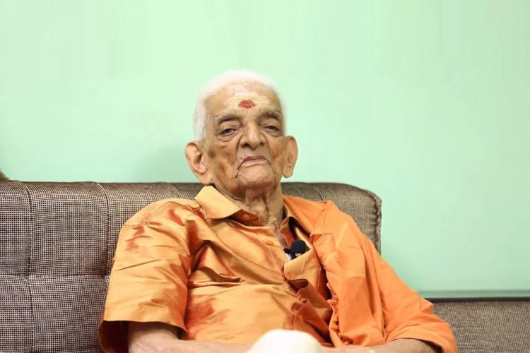 Elderly Unnikrishnan wearing an orange shirt sits on a brown couch