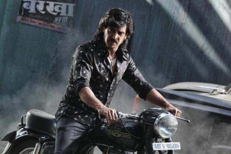 Upendra in a still from the movie Kabza He is wearing a black printed full-sleeve shirt and black trousers and is sitting on a motorcycle and looking to his right with a serious expression