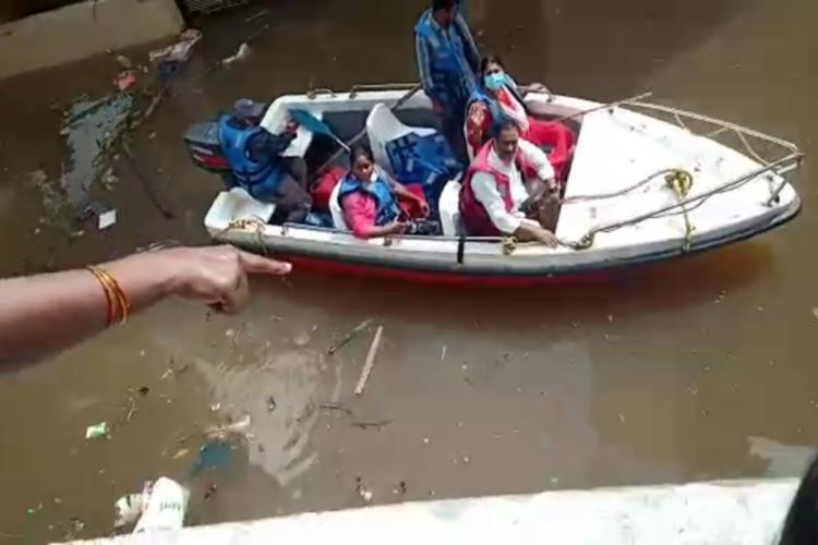 A womans hand with bangles extended as she talks to local MLA in a boat on the street