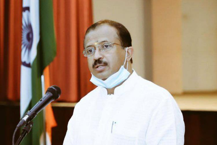 V Muraleedharan wears his mask on his chin and speaks into a mic with Indian flag on the background