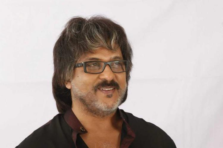 V Ravichandran in a black shirt smiling and looking to his left