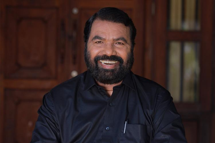 Sivankutty in a black shirt smiles and in the background is the entrance to a house