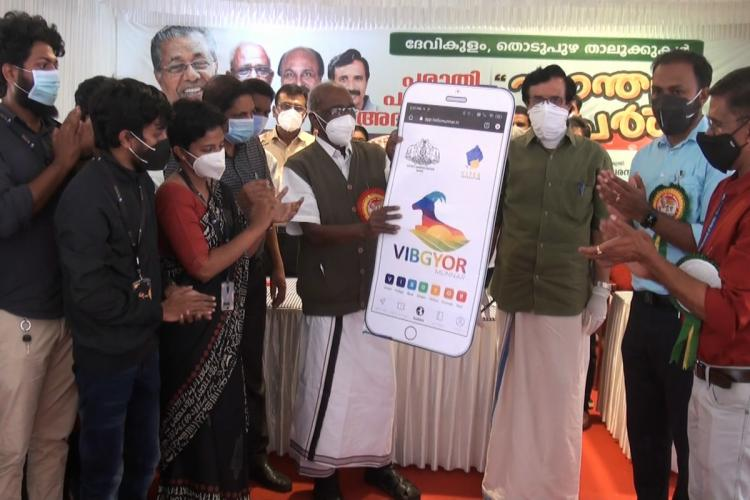 Power minister MM Mani and Education Minister C Raveendranath launch the Vibgoyor mobile app in Adimali Idukki A few others are seen on the stage as the ministers hold a cut-out of the mobile app