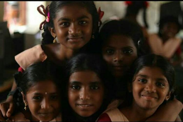 A group of young girls in school uniform smiling into the camera