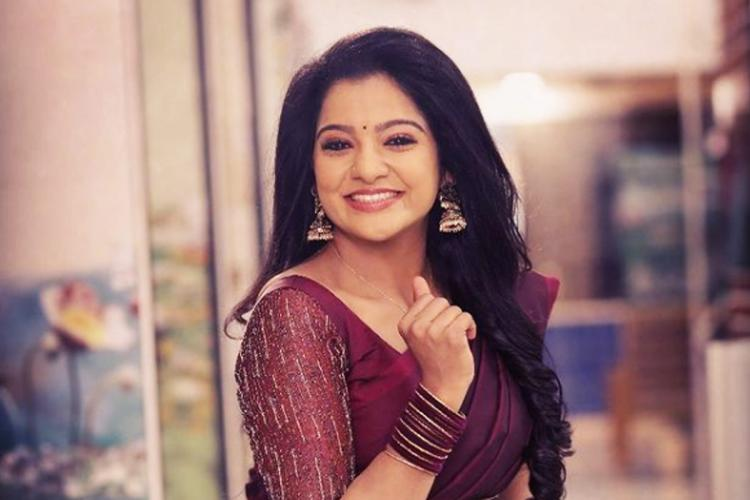 VJ Chitra in a purple saree and blouse as well as purple bangles head turn towards her right