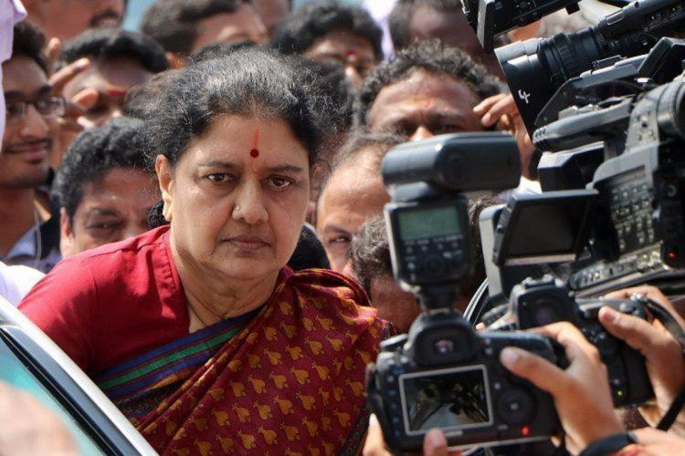 VK Sasikala surrounded by people and cameras as she gets out of her car