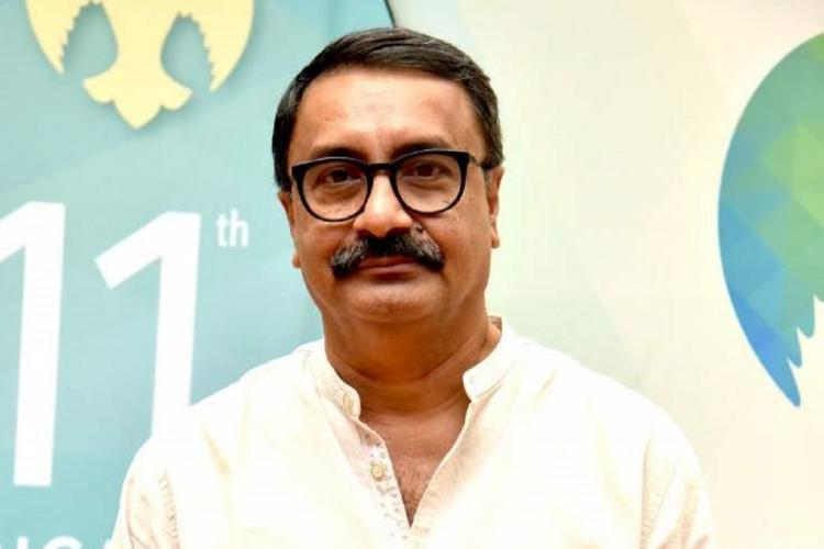 VK Prakash wears specs a white kurta and stands against a cream background with a green sticker