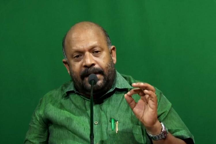 Sunil Kumar in a green shirt against a similarly green background is speaking gesturing with his left hand before a microphone