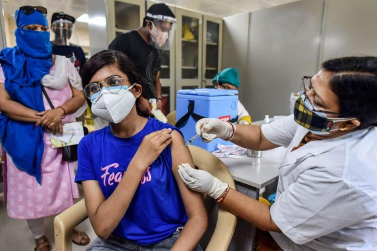 A woman in blue T-shirt getting vaccinated by a nurse