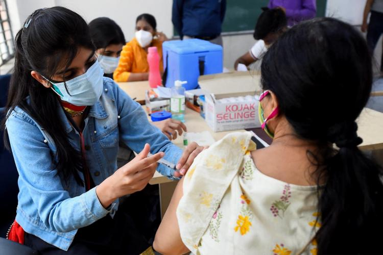 A young woman wearing a blue shirt is seen vaccinating a woman wearing a creme salwar