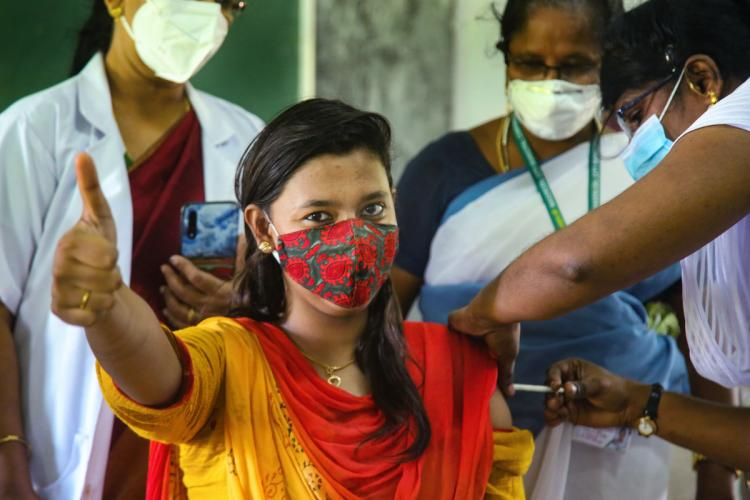 A woman wearing a mask gives the thumbs up as she gets vaccinated by a nurse in Kanniyakumari with other staff behind her