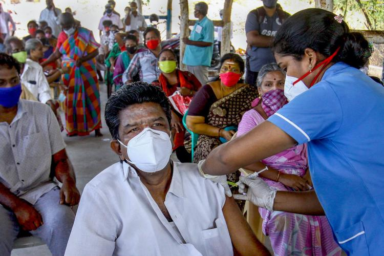 A man wears a mask as he gets the COVID-19 vaccine from a nurse while other beneficiaries sit waiting behind him in Chennai