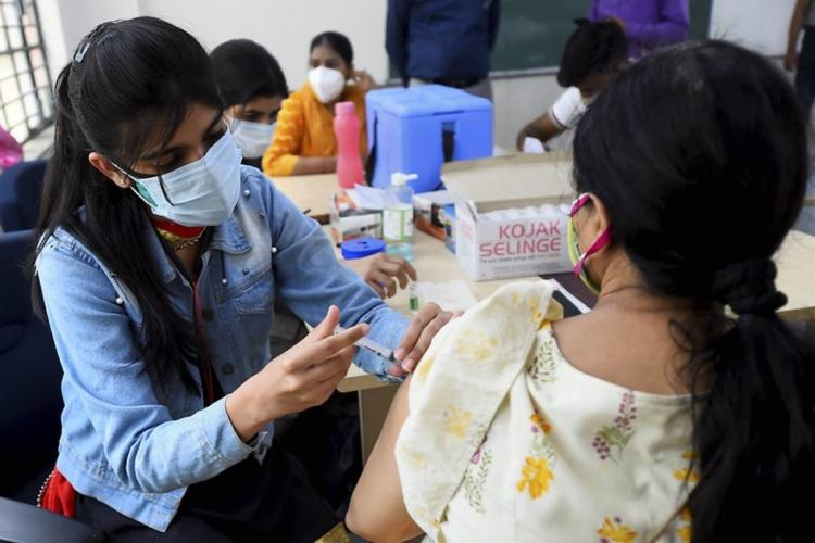 A health worker administers a dose of COVID-19 vaccine to a woman at a vaccination centre in New Delhi