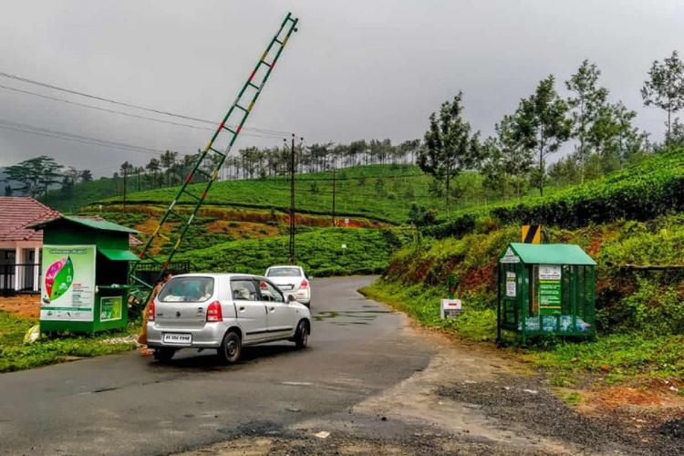 A green checkpost in Idukkis Vagamon showing a white car leaving the checkpost while a grey car waits at the checkpost The checkpost barrier is raised and a green booth to deposit waste can be seen opposite the checkpost