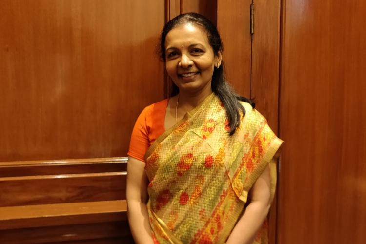 Valli Arunachalam standing against brown background, smiling slightly as she looks at the camera