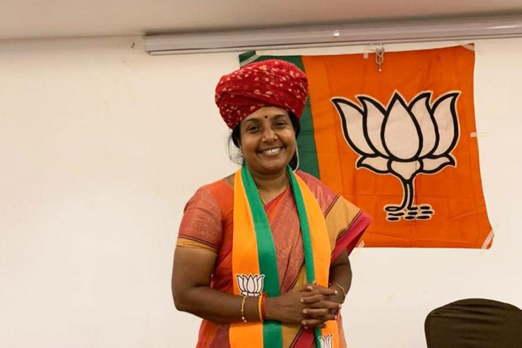 vanathi srinivasan with head turban in front of BJP flag
