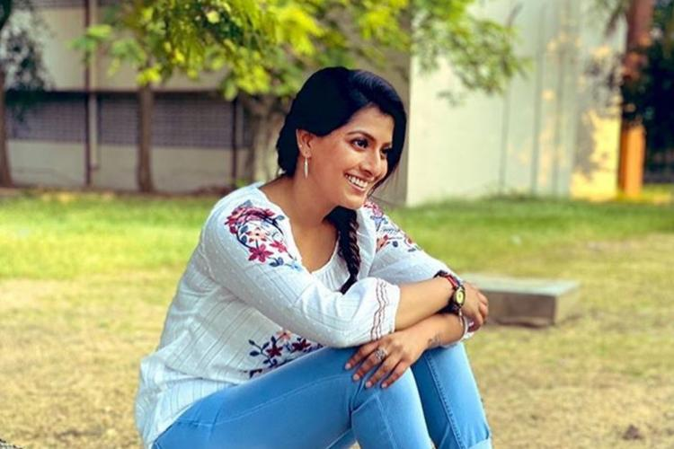 Varalaxmi Sarathkumar seated wearing a white shirt and blue jeans amidst greenery
