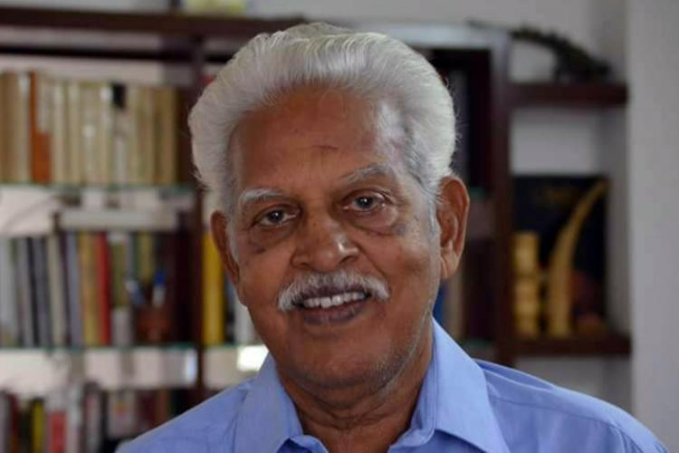Close up of Varavara Rao in a blue shirt smiling and looking into the camera with a shelf of books blurred in the background