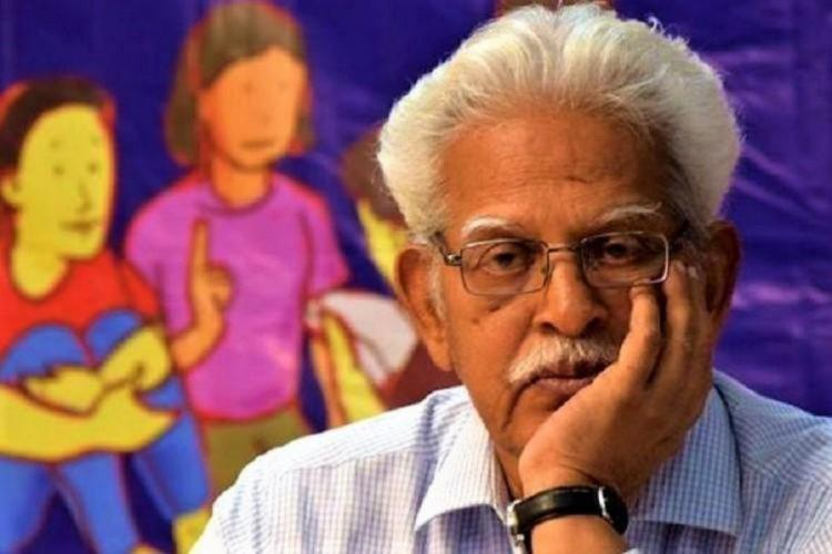 Varavara Rao with his hand on his face looking at the camera, there are colourful paintings of children in the backdrop