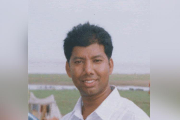 Father Varghese Palappallil wearing a white shirt standing in front of green fields