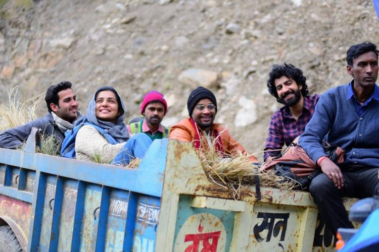 Six people are on a blue truck Parvathy in a white kurthi and blue shawl among them all of them smiling