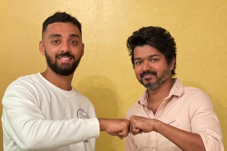 Vijay and Varun Chakravarthy fist bump against yellow wall