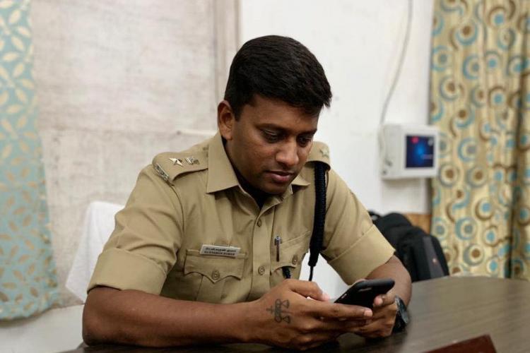 Varun Kumar IPS on his desk looking at phone