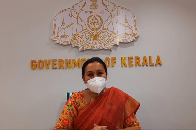 Veena George wearing an orange-brown Sari and a white mask sits in this video grab, against a white wall with the Government of Kerala logo