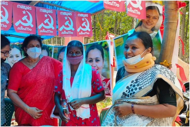 Kerala CPI M Candidate Veena George wearing neck collar and mask seeking votes
