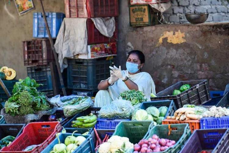 A vegetable seller sitting amid vegetables