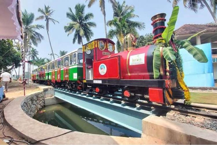 Red and green miniature train running on the rails of a beach side with trees in the background