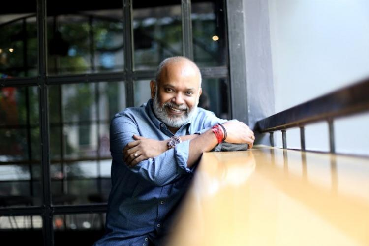 Director venkat Prabhu is seen wearing a blue shirt and is seen looking at the camera in photo