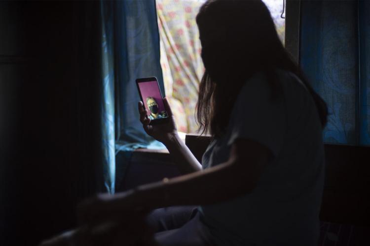 A woman on a video call with a person wearing a mask