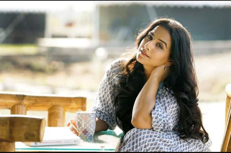 Vidya Balan sitting at a table with a coffee mug and a book