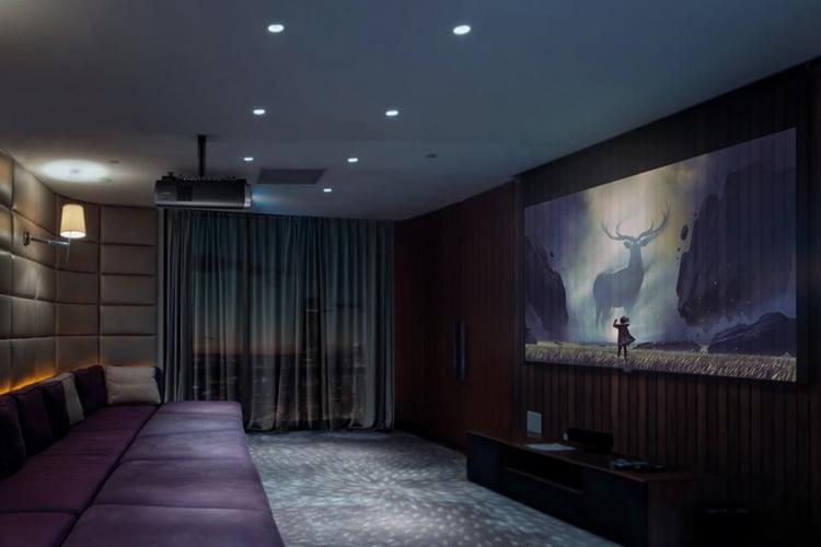 Image of sofa at one end of a room with a movie being projected on the wall opposite