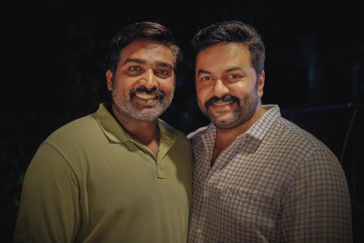 Actors Vijay Sethupathi and Indrajith Sukumaran posing smiling for the camera Vijay is in a dull green t-shirt while Indrajith is wearing a white checked shirt