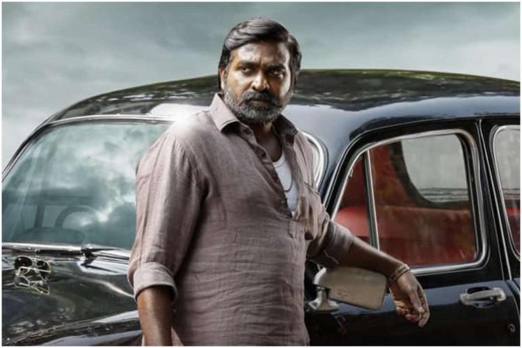Vijay Sethupathi stands in front of a black Ambassador car