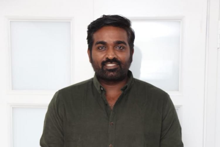 Vijay Sethupathi is seen smiling and striking a pose.