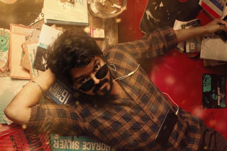 Vijay in Master poster lying down wearing sunglasses and surrounded by books