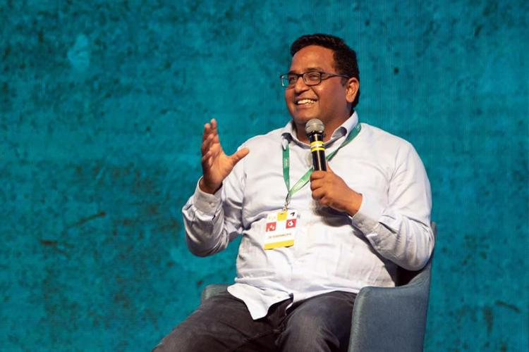 Paytm CEO Vijay Shekhar Sharma speaking at an event against a blue background wearing a white shirt and jeans