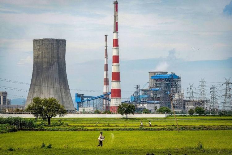 A farmer throws seed pesticides at a paddy field near the Dr Narla Tata Rao Thermal Power Plant in Vijayawada