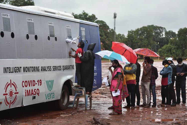 People lined up outside a mobile COVID sample collection bus in Vijayawada holding umbrellas ans standing in the rain