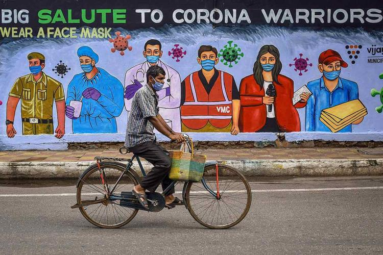 A man on a cycle goes past a painted wall with the words big salute to corona warriors wear a face mask