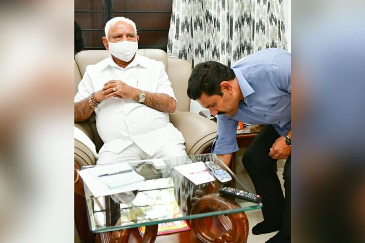 Vijayendra Yeddyurappa touches his father BS Yediyurappas feet Yediyurappa is wearing white pants white shirt and a white mask He is sitting on a chair