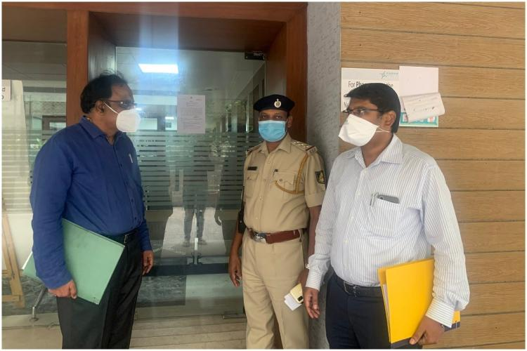 police personnel and health commissioner standing near the hospital OPD