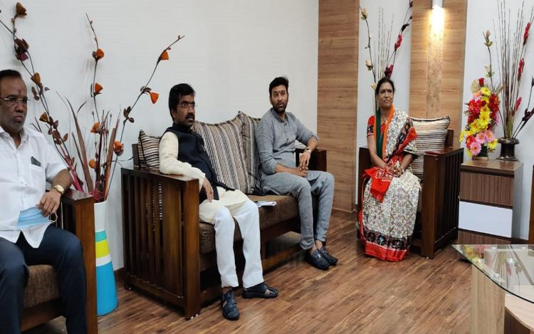 Vikram Goud wearing a cement coloured dress is sitting with three others on a sofa