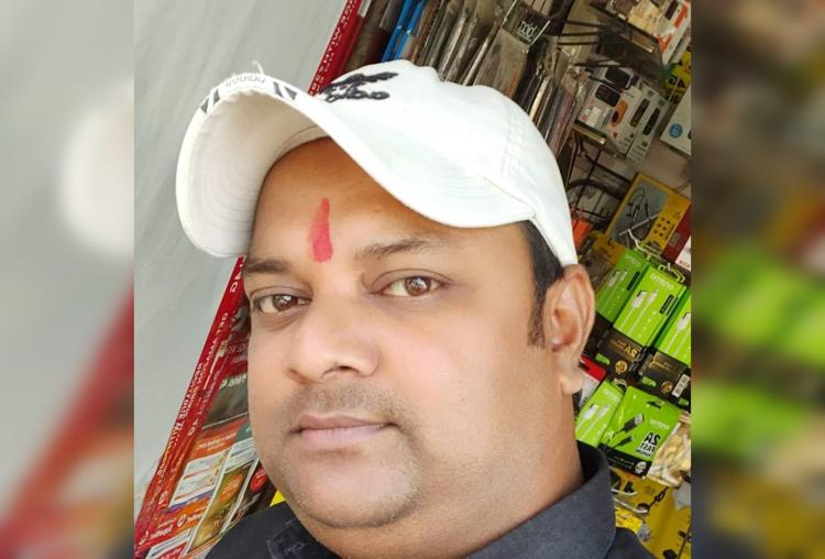 Face of a man with a white cap and a red tilak looking at the camera The collar of the dark shirt he is wearing can be seen