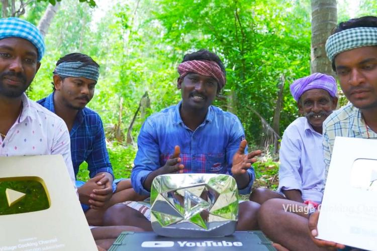 Team of Village Cooking channel displaying diamond button from YouTube while sitting on the ground